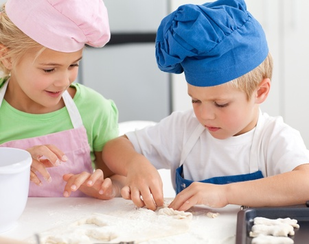 Young brother and sister kneading a dough to make cakes photo