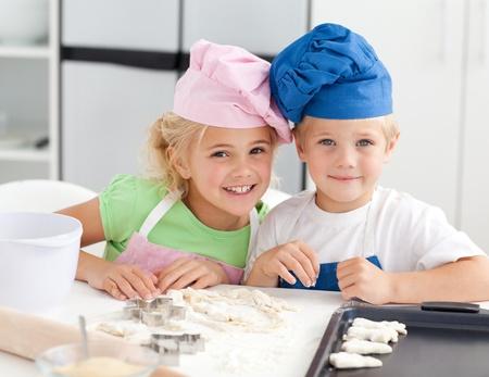 children cooking: Retrato de dos hijos adorables horneado en la cocina