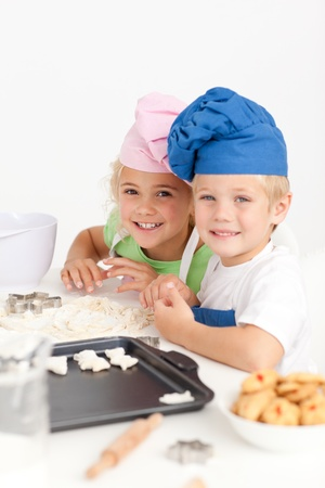 Two little chefs preparing cookies in the kitchen Stock Photo - 10215104