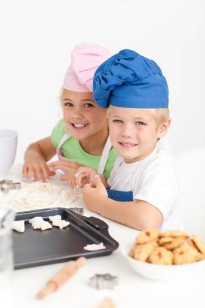 children cooking: Adorable siblings kneading together a dough in the kitchen