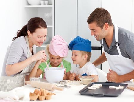 niños cocinando: Adorable familia hornear juntos en la cocina