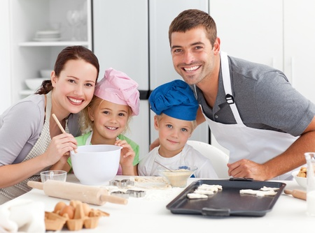Portrait of a joyful family cooking littles cakes  photo
