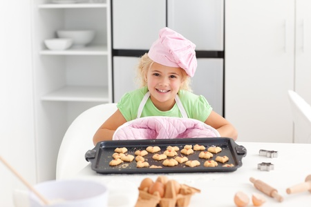 Happy little girl holding a plate with her cookies ready to eat photo