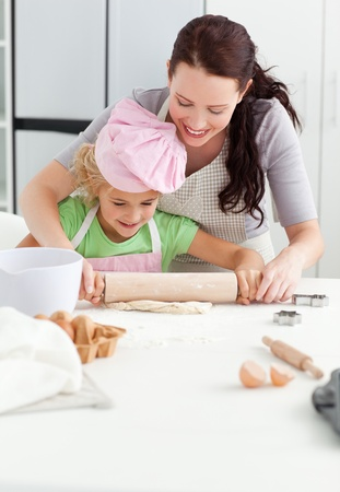 Beautiful mother and her cute daughter using a rolling pin Stock Photo - 10218591