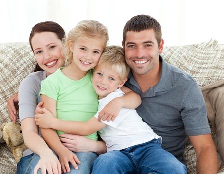 Adorable family sitting on the sofa and smiling photo