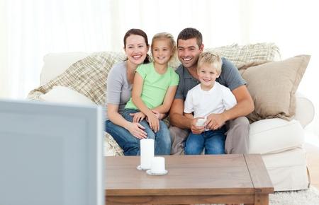viendo television: Adorable familia viendo televisión juntos sentado en el sofá