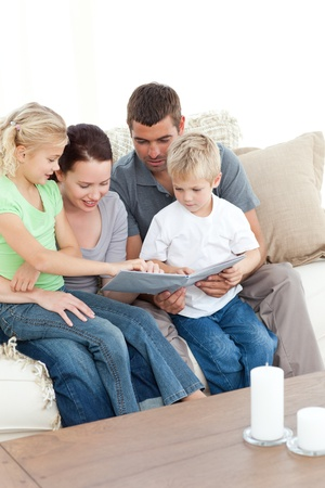 Happy family looking at a photo album sitting together in the living-room Stock Photo - 10198684