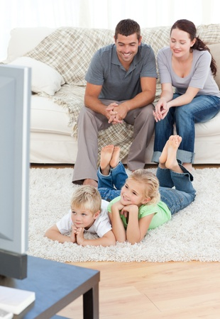 family movies: Adorable siblings watching television with their parents lying on the floor
