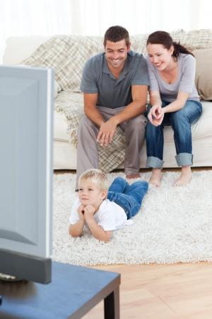 personas viendo television: Chico lindo ver la televisi�n en el piso con sus padres Foto de archivo