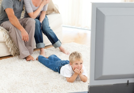 Attentive little boy watching television lying on the floor photo