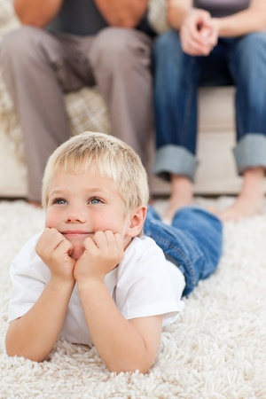 Cute little boy lying on the floor and watching television with his parents photo
