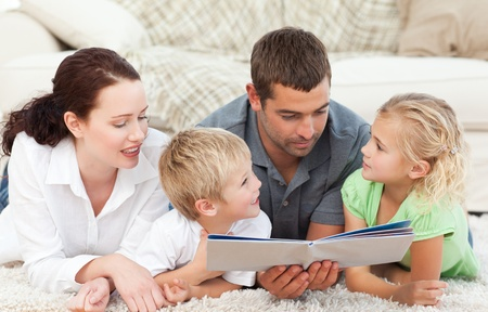 Family looking at a book on the floor  photo