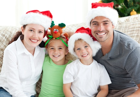 family on couch: Happy family with christmas hats sitting on the sofa
