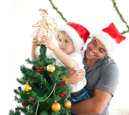 Happy father helping his son to put an angel on the Christmas tree Stock Photo - 10218270