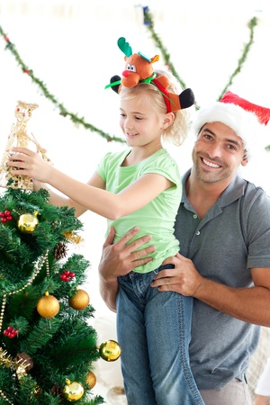 Happy father helping his daughter to put an angel on the Christmas tree