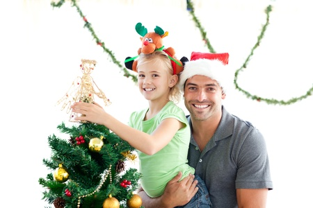 Happy father and daughter decorating together the christmas tree photo
