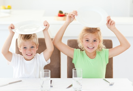 Funny brother and sister asking for their lunch raising their plates photo