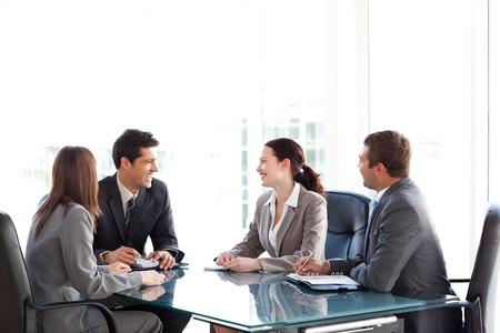 reunion de trabajo: Businessteam feliz hablando juntos durante una reuni�n