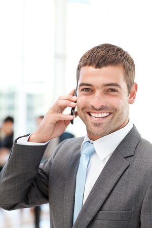 Happy hispanic businessman on the phone while his team is working photo