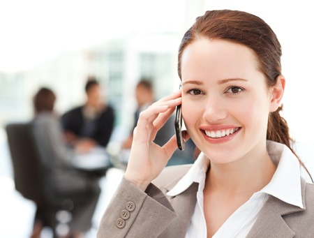 Attractive businesswoman on the phone while her team is working photo