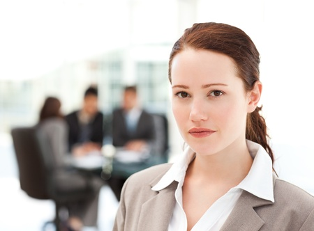 Charismatic businesswoman standing in the foreground while her team his working Stock Photo - 10214380