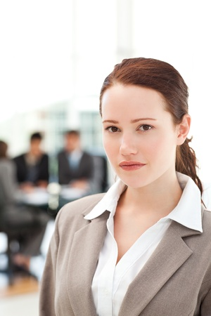 Serious businesswoman standing during a meeting with her team photo