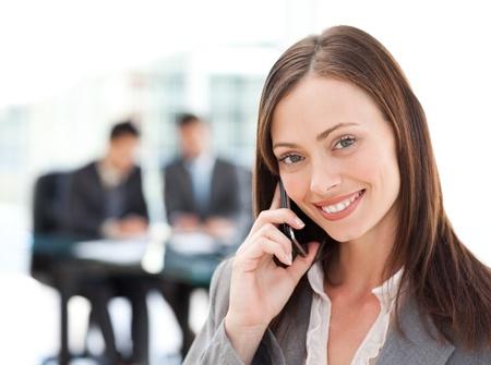 persona llamando: Cautivante empresaria en el teléfono, mientras que su equipo está trabajando Foto de archivo