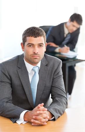 Charismatic businessman sitting in the foreground while his colleague is working photo