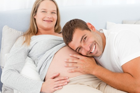 Portrait of a man listening the belly of his pregnant wife photo