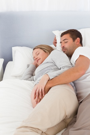 Lovely future parents sleeping in the bedroom photo
