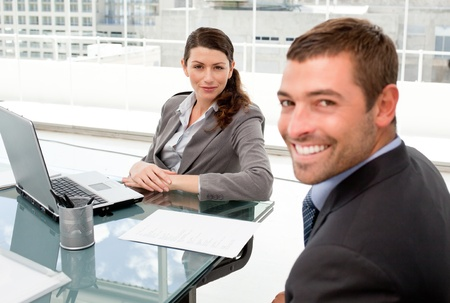 Happy businessman and businesswoman working together on a laptop photo