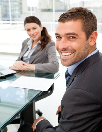 Cheerful business people sitting at a table with a laptop  photo