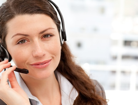 Pretty businesswoman with earpiece smiling at the camera photo