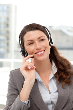earpiece: Cheerful businesswoman using earpiece sitting at her desk Stock Photo