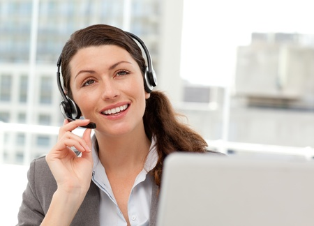 Thoughtful businesswoman talking on the phone while working on her computer Stock Photo - 10213589