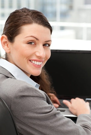 Rear view of a happy businesswoman working on her laptop photo