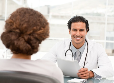 dring: Cheerful hispanic doctor dring an appointment with a patient Stock Photo