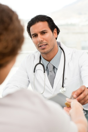 doctor giving pills: Serious doctor giving pills to his patient during an appointment Stock Photo