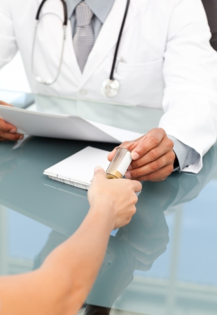doctor's appointment: Close up of a doctor giving medicine to his patient during an appointment