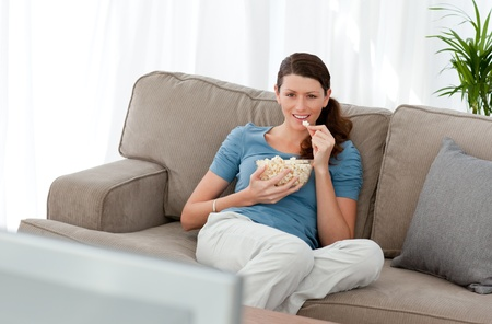 humoristic: Attractive woman watching television and eating pop corn on the sofa