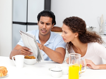 Serious man showing the newspaper to his wife during breakfast  photo