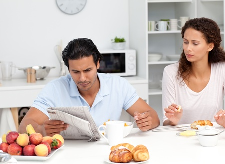 Concentrated couple reading the newspaper together during breakfast photo