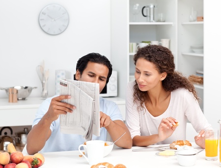 Happy couple reading the newspaper together during breakfast photo