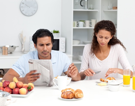 Lovely couple eating cereals and croissants together photo