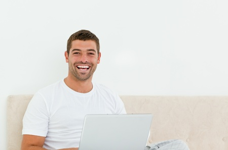 Happy man working on his laptop in his bedroom Stock Photo - 10206823