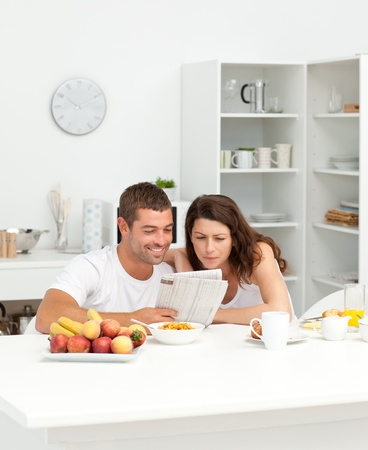 eating breakfast: Happy couple reading the newspaper in the kitchen