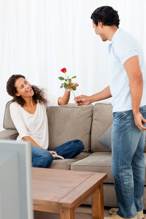 Adorable man giving a rose to his lovely girlfriend in the living room  photo