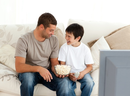Father and son watching television while eating pop corn on the sofa photo