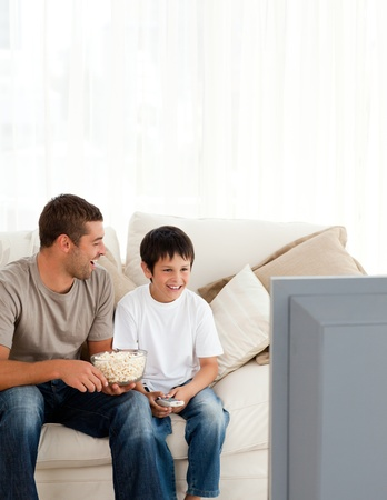 Happy boy watching television with his father on the sofa  photo