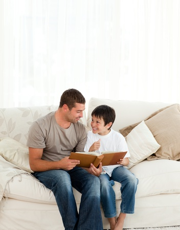 Adorable boy looking at a photo album with his father on the sofa  photo